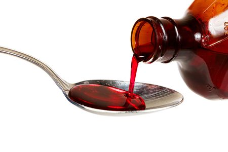 syrup: A bottle of cold medicine poured into a spoon Stock Photo