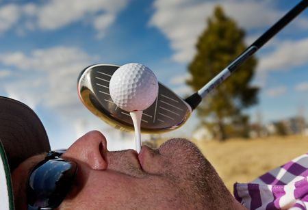 A golfer holding a tee in his mouth