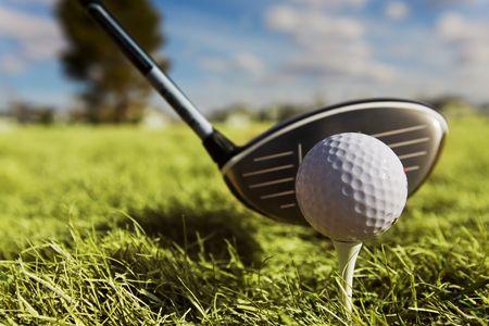 Una sfera e un driver di golf con il fuoco sulla sfera