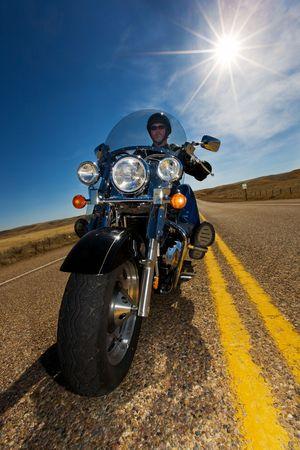 the rider: Un biker che gode un giro nel lato del paese un giorno pieno di sole