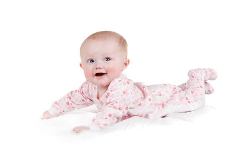 white sheet: A smiling  baby girl on a white sheet in Pajamas.