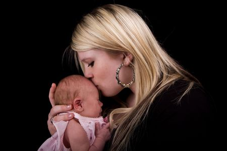 A young mother kissing her newborn girl