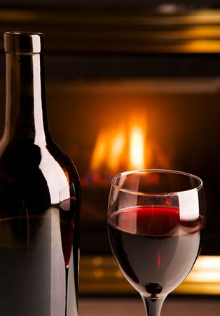 A bottle of red wine infront of a fireplace photo