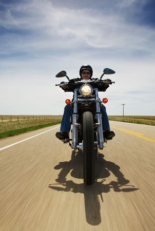 motorcycle rider: A biker speeding on a rural road Stock Photo
