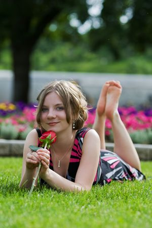 A Teenage girl relaxing at a park barefoot with a rose