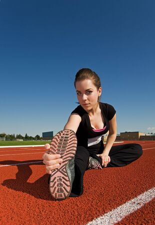 A beautiful woman stretching before a race at the track