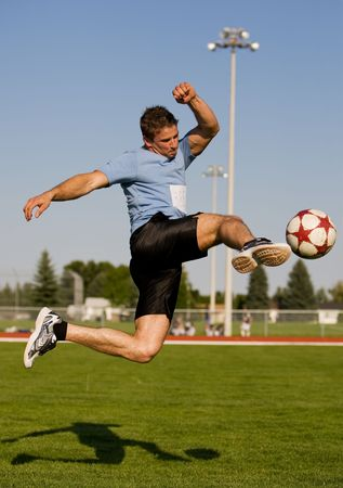 toughness: Athletic male in the air kicking a soccer ball