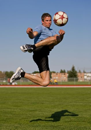 Athletic male in the air kicking a soccer ball photo