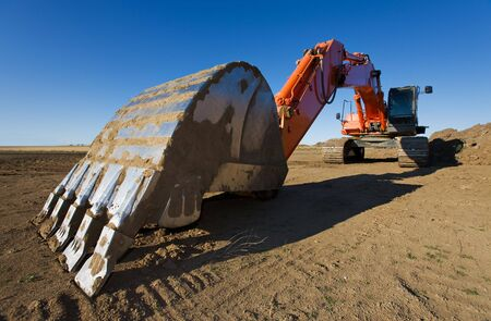 backhoe: A large orange backhoe parked at a construction site