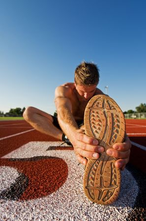 male athlete: A male athlete stretching at the race track
