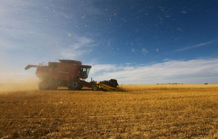 A combine harvester working with debris and dust flying Stock Photo - 3706755