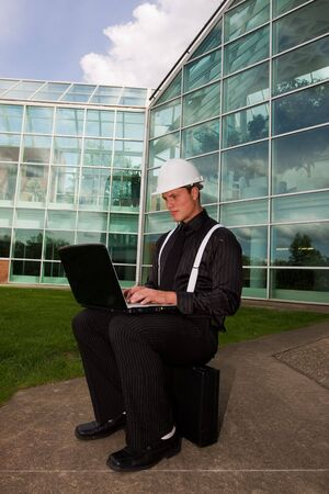 A young business man using a laptop outside Imagens