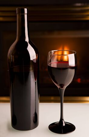 A bottle of red wine infront of a fireplace on a white table