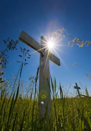 Old wooden crosses in a graveyard with sun flares