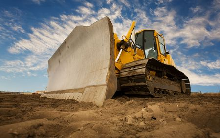 equipment: A large yellow bulldozer at a construction site low angle view Stock Photo