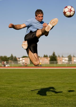 kicking: Athletic male in the air kicking a soccer ball