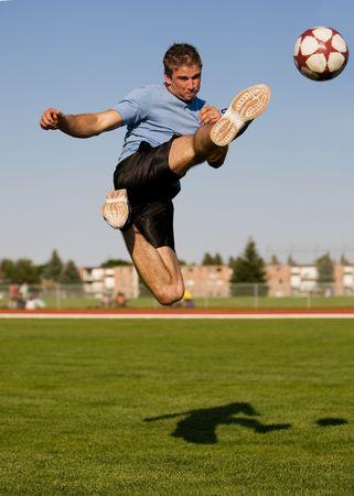 Atletische man in de lucht schopt een voetbal bal Stockfoto