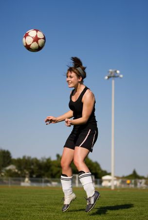 head shot: A female soccer player heading the soccer ball
