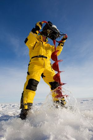 Ice fisherman drilling a hole with a power auger Stock Photo - 4132393