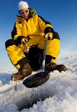 Ice fisherman cleaning ice from the hole with a ladle, focus on the scoop Stock Photo - 4136587