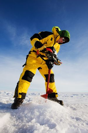 Ice fisherman drilling a hole on a frozen lake with a power auger  photo