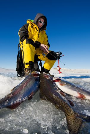 Ice fisherman with his catch of rainbow trout on the ice Stock Photo - 4175590