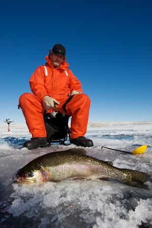 Ice fisherman with a large rainbow trout on the ice Stock Photo - 4206927