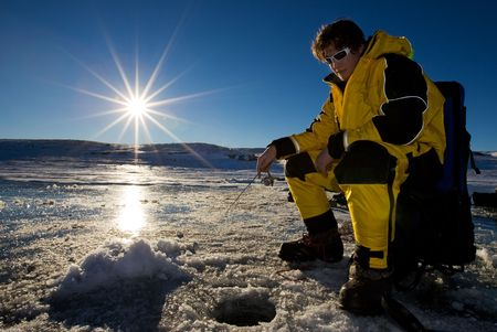Fisherman enjoying a day on the ice with a low setting sun Stock Photo - 4207001