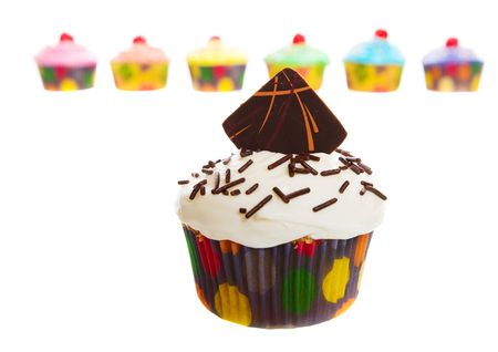 A homemade cupcake with colorful cakes in the background photo