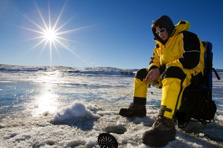 Fisherman enjoying a day on the ice on a bright sunny day Stock Photo - 4504966