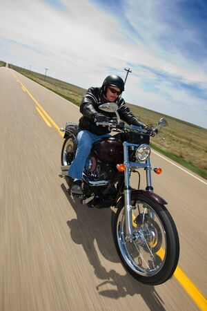 A biker taking a ride on a long strait rural road, tilted view