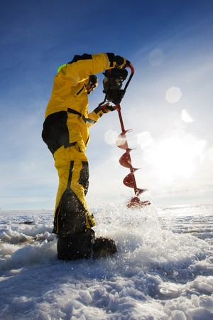 auger: Ice fisherman drilling a hole with a power auger with sun flares