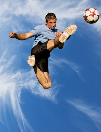 kicking ball: Athletic male high in the air kicking a soccer ball Stock Photo