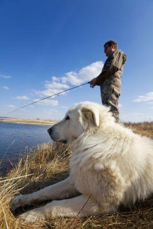 A man and his dog enjoying a day together at the lake photo