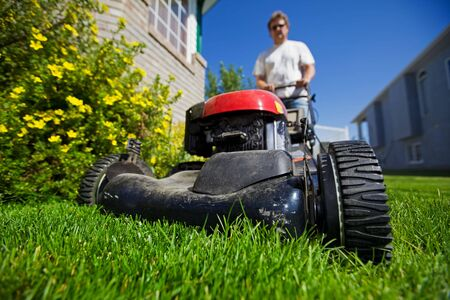 A man mowing the front lawn with focus on the front wheel photo