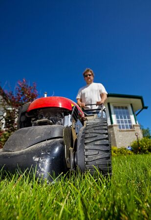 man mowing the front lawn with focus on the front  photo