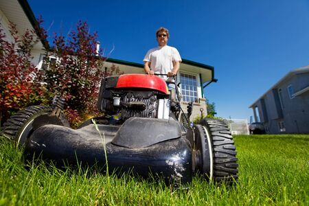A man mowing the front lawn with focus on the front  photo