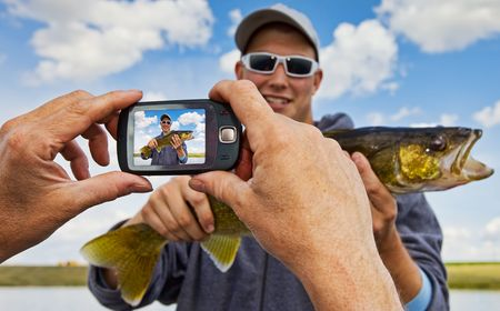 A proud fisherman posing with his catch having his picture taken photo