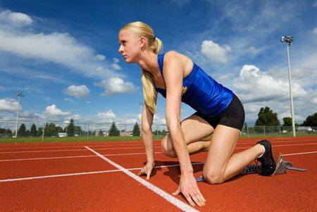 A teen athlete ready to race in the starting blocks