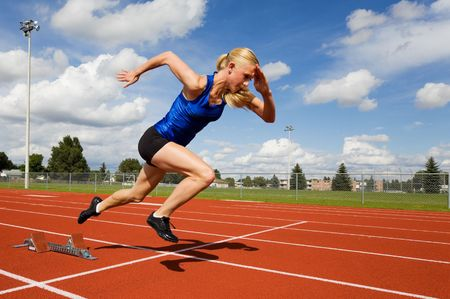 Track athlete exploding out of the starting blocks photo