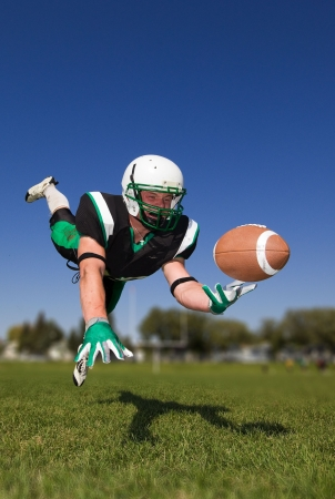 American football player diving and catching the ball Stock Photo - 5773558