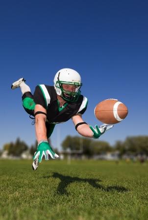 catch: Giocatore di football americano, immersioni e cattura la palla  Archivio Fotografico