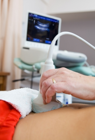 Scanning a female stomach with a ultrasound machine focus on the prob. Stock Photo - 5860542