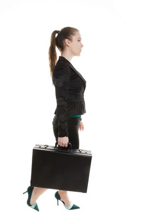 A young business woman walking with a suitcase