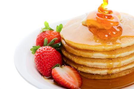 パンケーキとメープル シロップとイチゴの上に注がれる