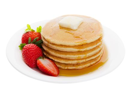 hotcakes: Plate full of fluffy golden pancakes with strawberries and maple syrup
