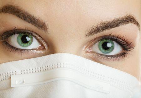 緑色の目でマスクを着ている看護婦のクローズ アップ