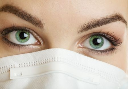 A closeup of a nurse wearing a mask with green eyes photo