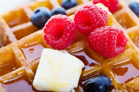 Closeup of waffles with mixed fruit and maple syrup photo