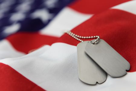 veterans day: Blank dog tags on American flag with focus on tags - Shallow dof